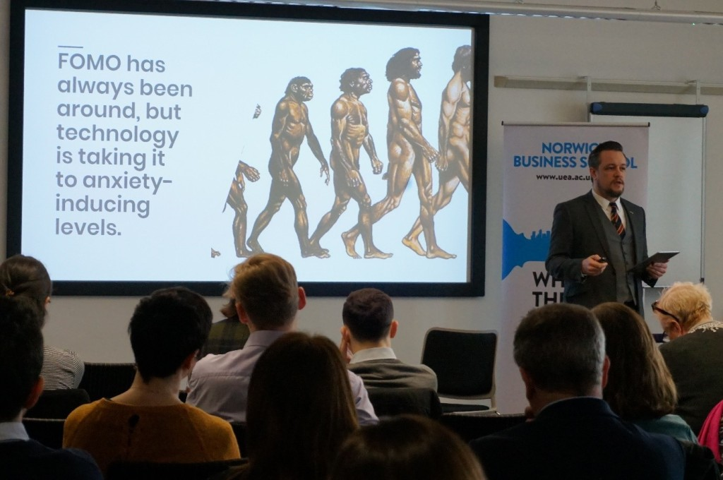 """James Gill presenting to a room of people. On the presentation slide it says """"FOMO has always been around, but technology is taking it to anxiety inducing levels"""""""